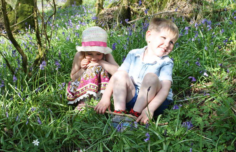 Boy and a girl sitting in a bluebell wood